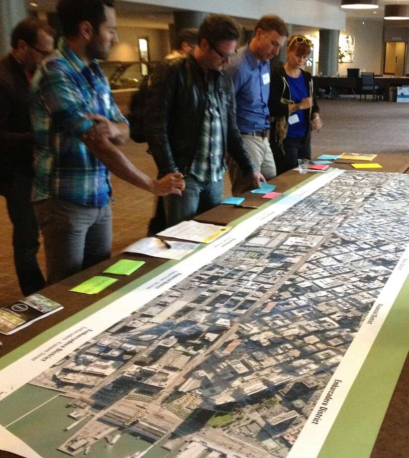 Workshop attendees poring over an overall plan for Market Street.
