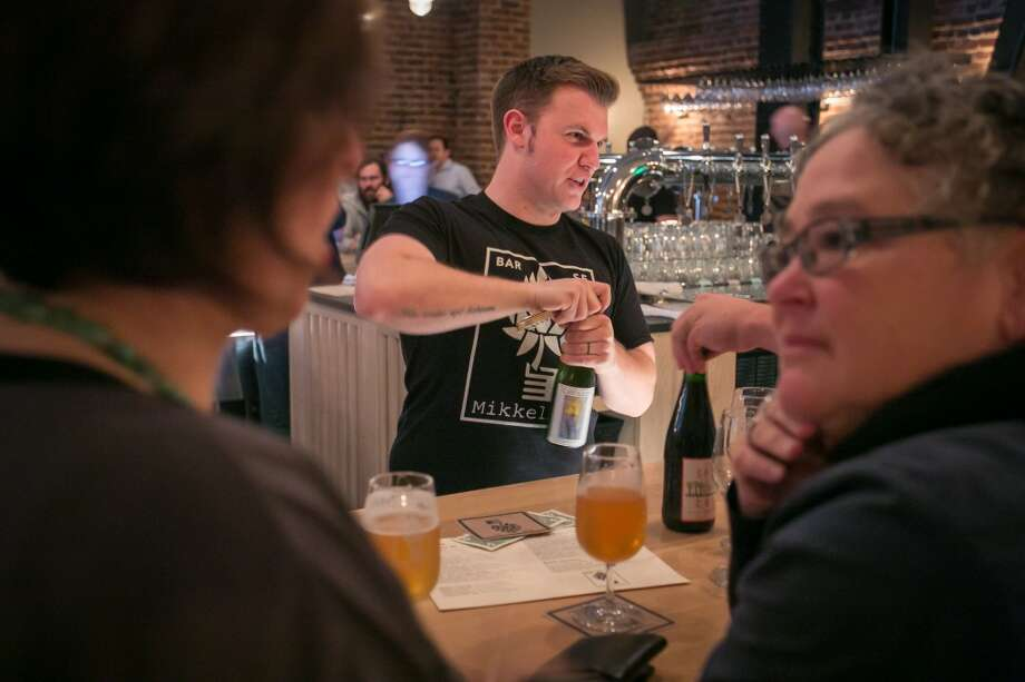 A bartender opens a beer at Mikkeller in San Francisco.