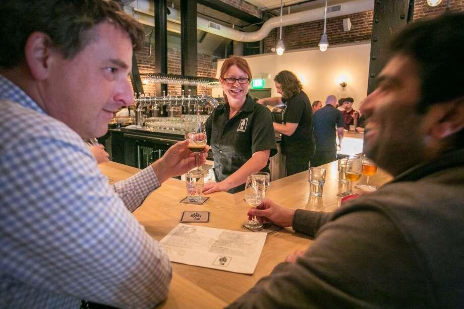 Bartender Kirby Bennett talks with customers at Mikkeller.
