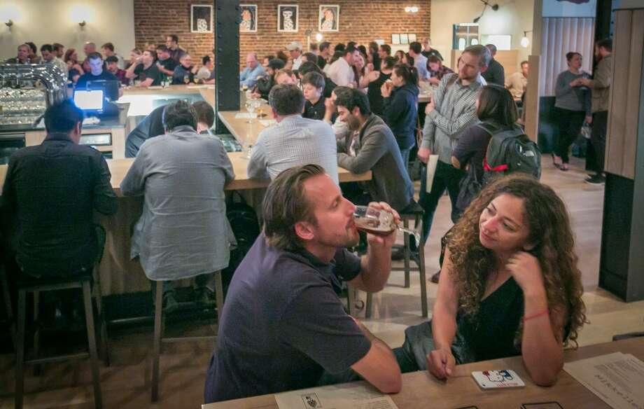 People enjoy beers at Mikkeller in San Francisco.