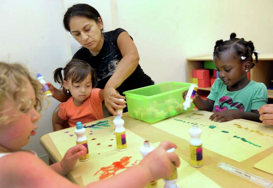 Head Start lead teacher Carmen Prybylski works with children from left, Quinn Watson, 3, Sofia Coway, 2, and Kayla Lamour, 3, Wednesday, July 17, 2013, at the new Head Start building on Foster Street in Danbury, Conn. Photo: Carol Kaliff / The News-Times
