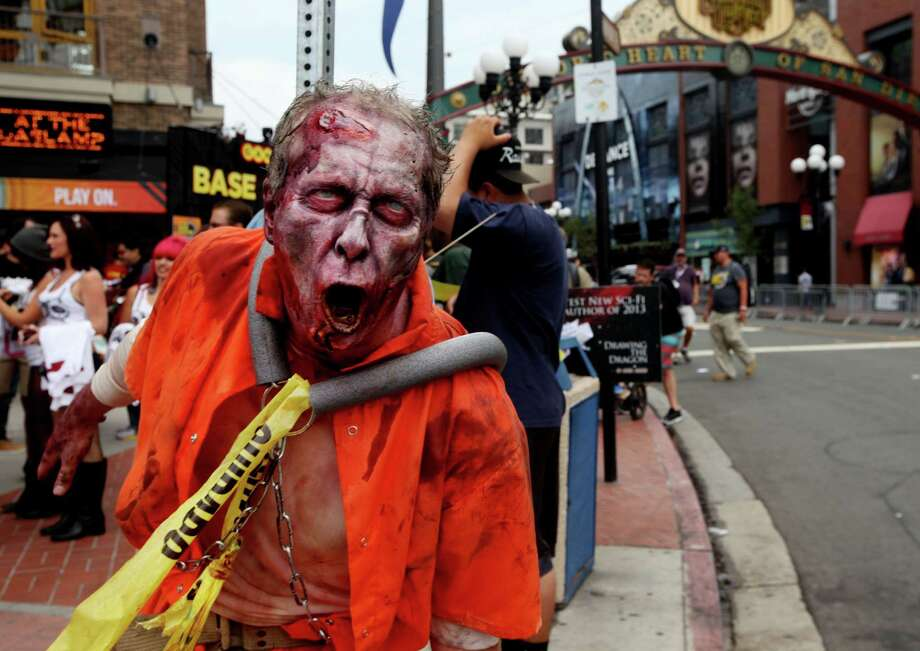A zombie character greets people along 5th Avenue in the Gaslamp Quarter at Comic Con on July 19, 2013 in San Diego, California.  Comic Con International Convention is the world's largest comic and entertainment event and hosts celebrity movie panels, a trade floor with comic book, science fiction and action film-related booths, as well as artist workshops and movie premieres. Photo: Sandy Huffaker, Getty Images / 2013 Getty Images