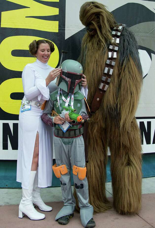 Jamie Craig (L) and her husband Sam Craig (R) and son Aidan Craig wear Star Wars costumes outside the San Diego Convention Center on the second day of Comic-Con International 2013 in San Diego, California, on July 19, 2013. Comic-Con is a four-day geekfest of pop culture attended by some 130,000 devotees of comic books, movies and TV shows -- many dressed up in the costumes of their idols. Photo: ROBYN BECK, AFP/Getty Images / AFP