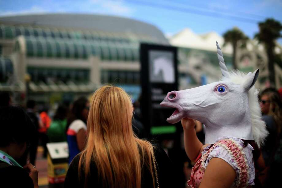 A woman with a unicorn horse head waits in line to cross the street at Comic Con at the San Diego Convention Center on July 19, 2013 in San Diego, California.  Comic Con International Convention is the world's largest comic and entertainment event and hosts celebrity movie panels, a trade floor with comic book, science fiction and action film-related booths, as well as artist workshops and movie premieres. Photo: Sandy Huffaker, Getty Images / 2013 Getty Images