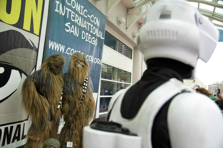 A Storm Trooper walks by two Chewbacca, also known as Chewie, a fictional character in the Star Wars franchise, at the Comic-Con International 2013 at the San Diego Convention Center  in San Diego California July 19, 2013.   Comic-Con is a four-day geekfest of pop culture attended by some 130,000 devotees of comic books, movies and TV shows -- many dressed up in the costumes of their idols. Photo: ROBYN BECK, AFP/Getty Images / AFP