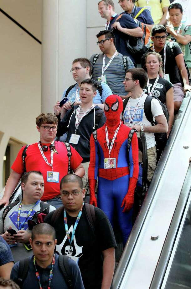 In this Thursday, July 18, 2013 photo, attendees, including one dressed as Spider-Man, ride down an escalator at  Comic-Con, in San Diego. Photo: Charlie Neuman, Associated Press / The U-T San Diego