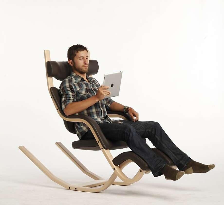 Collin Ferry of ergodepot demonstrating the Balans chair ($2,195), an unusual design that allows the user to rock from kneeling to sitting to reclining. Photo: Craig Lee, The Chronicle