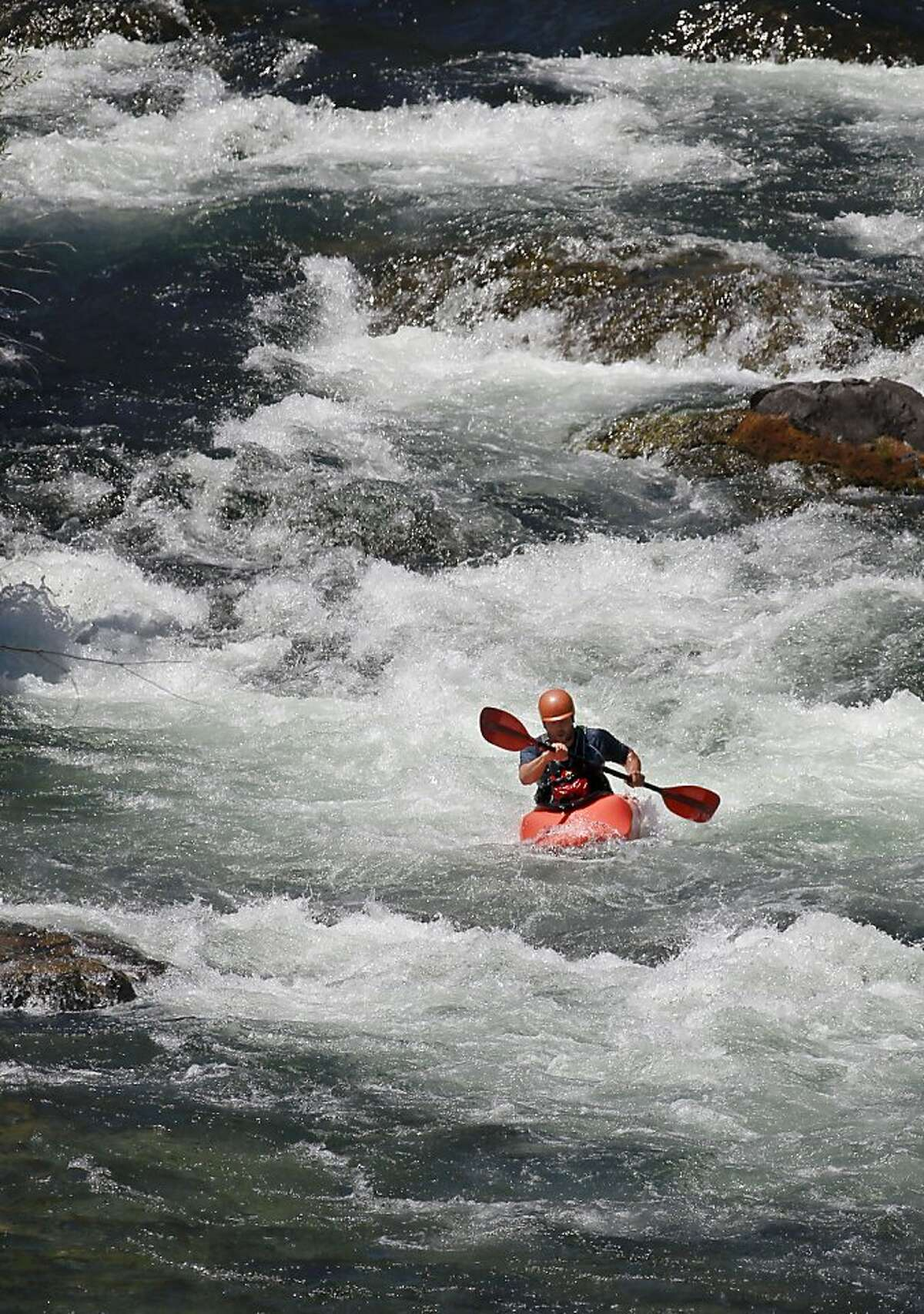 Nick Walker of Weaverville kayaks the rapids of the Trininty River below Lewiston Dam in Lewiston, Calif on Friday July 19, 2013. Low water and a giant salmon run has created concern about a fish die off in the Klamath River similar to what happened in 2002. The Bureau of Reclamation is proposing releases of water from Trinity Dam to help fish but agriculture interests have threatened to block the idea.