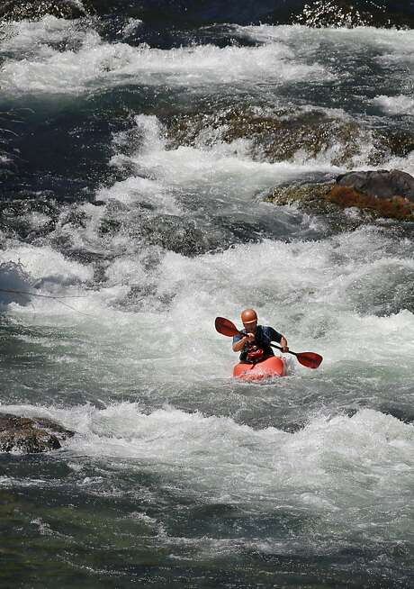 Nick Walker kayaks rapids in the Trinity River, from which officials want to divert water to the Klamath to protect salmon (below) in a low-water year. Photo: Michael Macor, San Francisco Chronicle