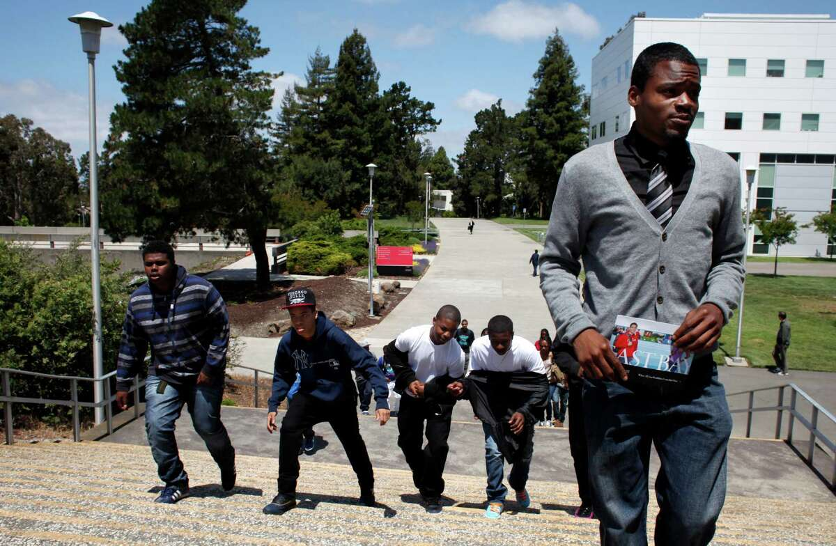 Melvin Thomas, left, Marcell Stargetti, Anthony Dennis, Roashon Wilson, follow a tour guide as they visit the campus of Cal State East Bay in Hayward on a field trip in 2013 with the manhood development class.
