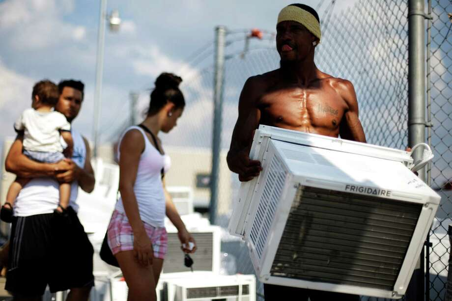 Salesman Lu Pichardo carries a customer's air conditioner at Appliances R Us, Thursday, July 18, 2013, in Philadelphia. An excessive heat warning is again in effect for the Philadelphia region with highs expected to head up to the high-90s Photo: Matt Rourke, Associated Press / AP