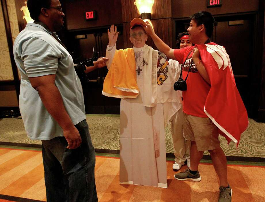 Ronnie Piper, left, with William Cruz, center and Mitchell Nguyen, right adjust a cardboard cut out of the Pope Francis dressed up in University of St. Thomas gear after it fell over at the Hilton-Americas Hotel at the start of this weekend's Archdiocese of Galveston-Houston's Archdiocesan Youth Conference (AYC), Friday, July 19, 2013, in Houston. Photo: Karen Warren, Houston Chronicle / © 2013 Houston Chronicle