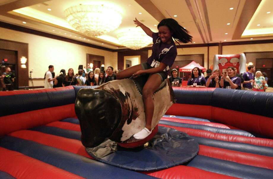 Cori Barnes, 14, with St. Helen's Church in Pearland, tries to hang onto a mechanical bull set up at the Hilton-Americas Hotel at the start of this weekend's Archdiocese of Galveston-Houston's Archdiocesan Youth Conference (AYC), Friday, July 19, 2013, in Houston. Photo: Karen Warren, Houston Chronicle / © 2013 Houston Chronicle