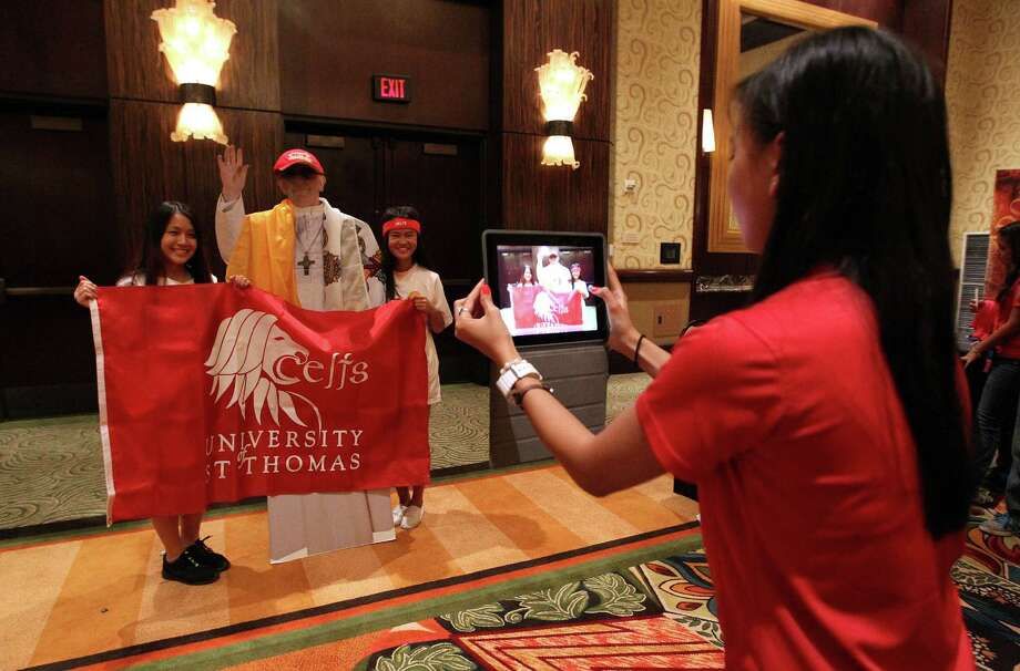 "Christine Khuong, 18, left, and Monique Le, 17, get their photo taken with a cardboard cut out of the Pope Francis dressed up in University of St. Thomas gear in the ""Bayou Village"" set up in a ballroom at the Hilton-Americas Hotel at the start of this weekend's Archdiocese of Galveston-Houston's Archdiocesan Youth Conference (AYC), Friday, July 19, 2013, in Houston. Photo: Karen Warren, Houston Chronicle / © 2013 Houston Chronicle"