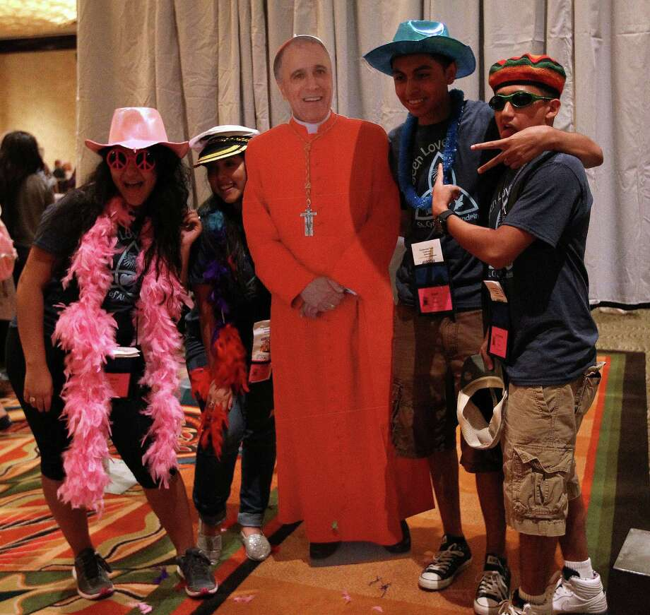 Hilian Gonzalez, 17, Evelyn Bueno, 16, with Jerry Aviles, 16, and Alejandro Luna, 16, from St. Cyril of Alexandria  get their photo taken with a cardboard cutout of Cardinal DiNardo in a photo booth at the Hilton-Americas Hotel at the start of this weekend's Archdiocese of Galveston-Houston's Archdiocesan Youth Conference (AYC), Friday, July 19, 2013, in Houston. Photo: Karen Warren, Houston Chronicle / © 2013 Houston Chronicle