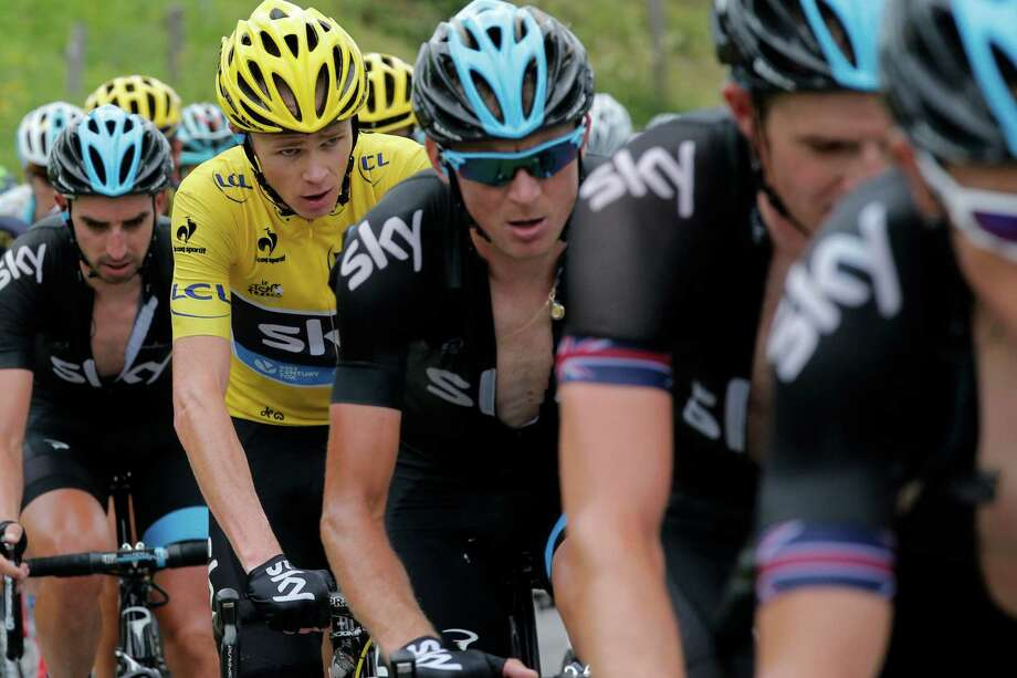 Christopher Froome of Britain, wearing the overall leader's yellow jersey, rides with his teammates during the nineteenth stage of the Tour de France cycling race over 204.5 kilometers (127.8 miles) with start in in Bourg-d'Oisans and finish in Le Grand-Bornand, France, Friday July 19 2013. (AP Photo/Christophe Ena) ORG XMIT: PDJ116 Photo: Christophe Ena / AP