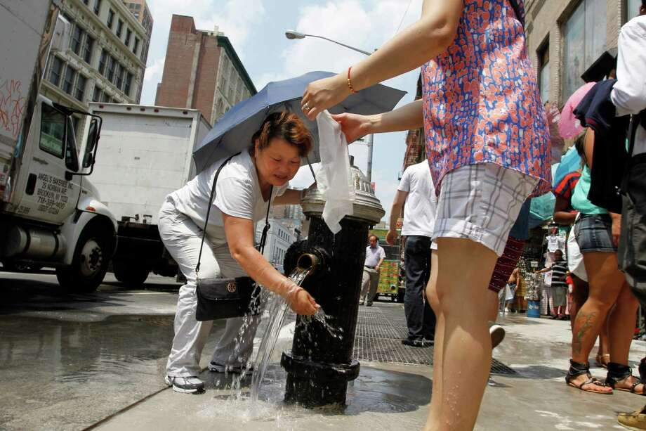 A woman sheltering from the sun under an umbrella cools herself with water from a fire hydrant on Canal Street in New York's Chinatown Friday, July 19, 2013. A punishing heat wave continues to scorch New York, threatening to break heat records and putting a huge strain on the state's overworked power grid. (AP Photo/Jon Gerberg) ORG XMIT: NYR102 Photo: Jon Gerberg / AP