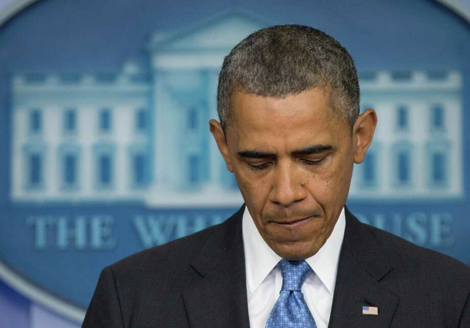 President Barack Obama pauses as he speaks during the daily news briefing at the White House, Friday, July 19, 2013, in Washington, about the fatal shooting of Trayvon Martin by George Zimmerman. (AP Photo/Carolyn Kaster) ORG XMIT: DCCK109 Photo: Carolyn Kaster / AP