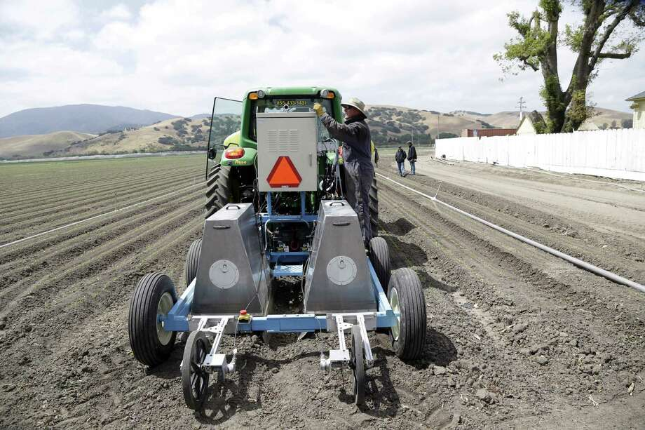 Field operations manager Matthew Rossow tests the Lettuce Bot in Salinas, Calif.   The boxy robotic machine can thin fields of lettuce 20 times faster than a person. Photo: Marcio Jose Sanchez / Associated Press