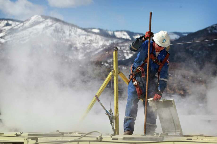 "In this March 29, 2013 photo, a worker checks a dipstick to check water levels and temperatures in a series of tanks at an Encana Oil & Gas (USA) Inc. hydraulic fracturing operation at a gas drilling site outside Rifle, Colorado. Hydraulic fracturing, or A'A""fracking,A'A"" can greatly increase the productivity of an oil or gas well by splitting open rock with water, fine sand and lubricants pumped underground at high pressure. Companies typically need several million gallons of water to frack a single well. In western Colorado, Encana says it recycles over 95 percent of the water it uses for fracking to save money and limit use of local water supplies. (AP Photo/Brennan Linsley) Photo: Brennan Linsley / AP"
