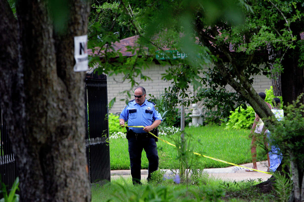 An officer tapes off a home on Friday in north Houston where four men told police they were locked in and not allowed to leave.