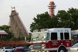 Emergency personnel are on the scene at Six Flags Over Texas in Arlington, Texas, after a woman died on the Texas Giant roller coaster, background left, on Friday, July 19, 2013. (AP Photo/The Dallas Morning News, Tom Fox)  MANDATORY CREDIT; MAGS OUT; TV OUT; INTERNET USE BY AP MEMBERS ONLY; NO SALES