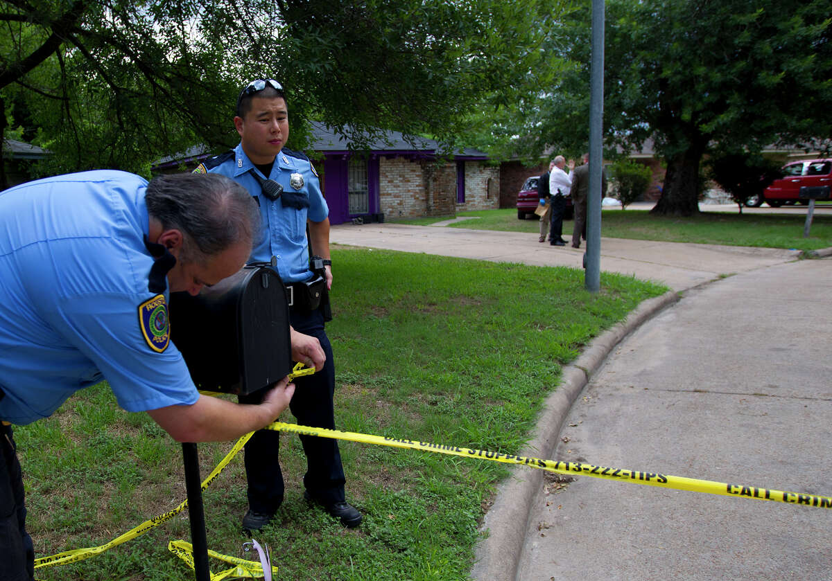 A policeman ties police tape at the scene where four individuals were held captive in the 8600 block of White Castle in Houston, Friday, July 19, 2013, in Houston. Police found four men held against their will in the home in deplorable conditions after they responded to a 911 call that brought police to the north Houston home described as a