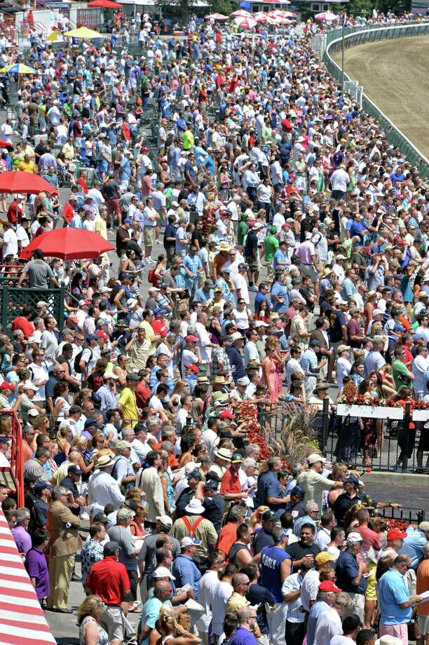 Horse racing fans watch the running second race of opening day at Saratoga Race Course Saratoga Springs, NY, Friday July 19, 2013.  (John Carl D'Annibale / Times Union) Photo: John Carl D'Annibale / 10023139A