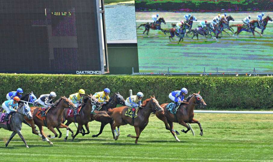Horses run past a giant video screen at the start of the second race of opening day at Saratoga Race