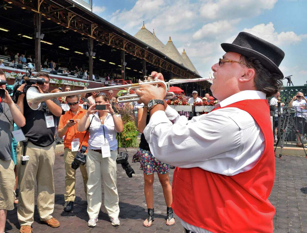 """Sam """"The Bugler"""" Grossman blows call to post on opening day at Saratoga Race Course Saratoga Springs, NY, Friday July 19, 2013. (John Carl D'Annibale / Times Union)"""