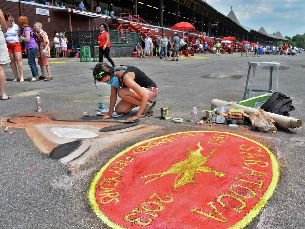 Tori Rodriguez of Ballston Spa creates a chalk art rendering of the Saratoga 150 logo in front of the grandstands on opening day at Saratoga Race Course Saratoga Springs, NY, Friday July 19, 2013. (John Carl D'Annibale / Times Union)