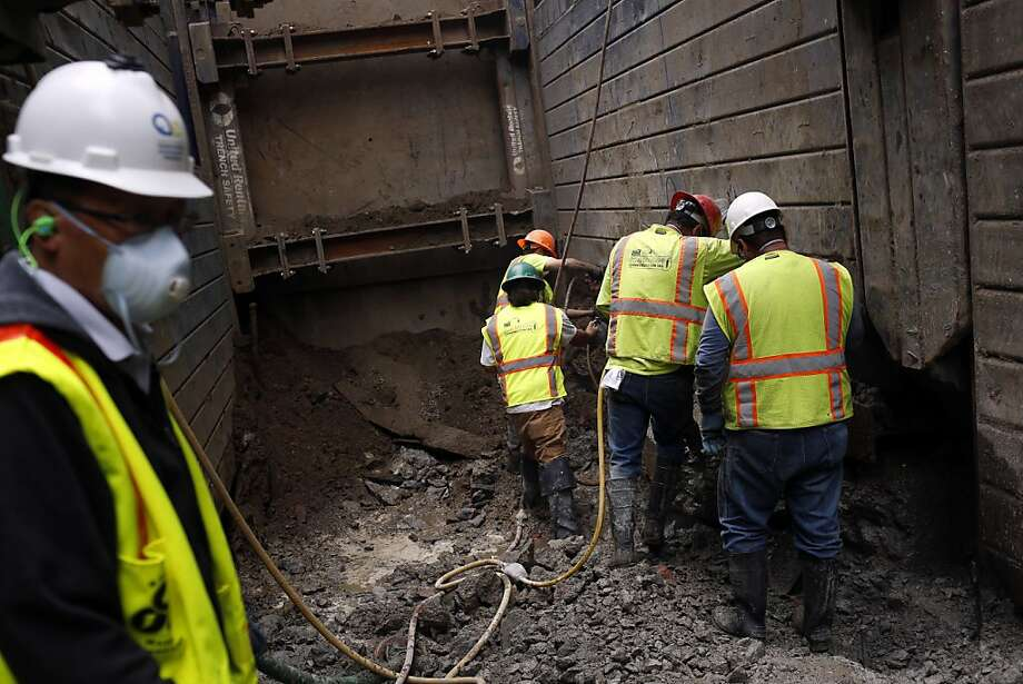 Construction workers drill through old concrete foundations to create a redundant sewer system at Drumm Street. Nearly 160 miles of pipes in San Francisco are at a high risk of failure. Photo: Ian C. Bates, The Chronicle