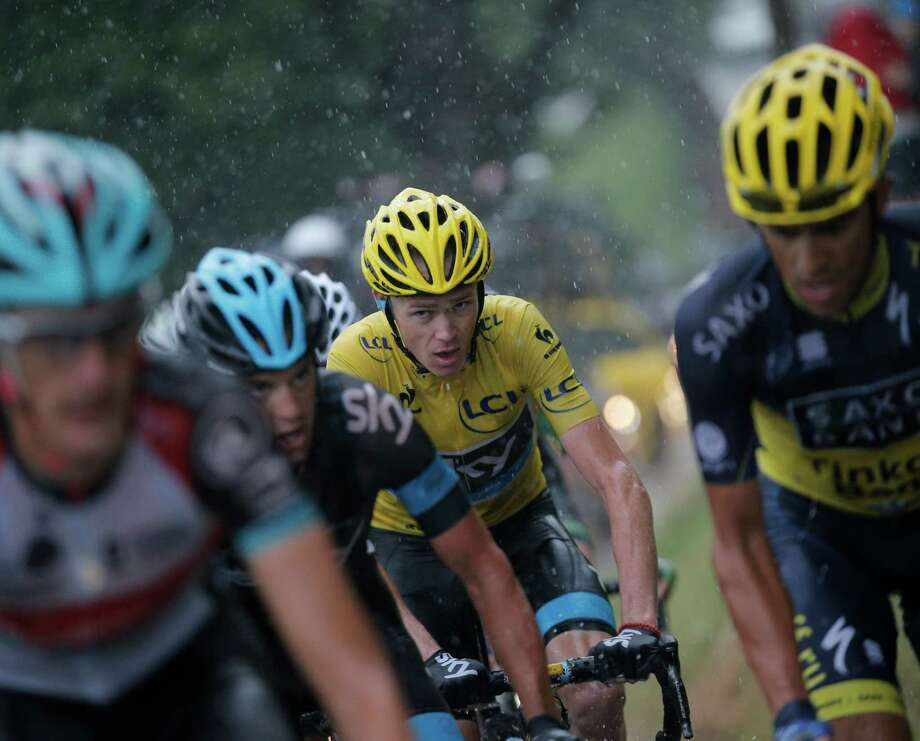 Overall leader Chris Froome, center, keeps his eyes on what's ahead as he ascends the Col de la Croix Fry during Friday's 19th stage of the Tour de France. Photo: Christophe Ena, STF / AP