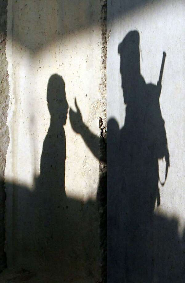 The shadow of a member of the Israeli security forces gesturing towards a Palestinian Muslim youth is seen as on a wall of a checkpoint along Israel's controversial separation barrier on the outskirts of the West Bank town of Bethlehem as many Palestinians head to Jerusalem to attend the Friday prayers at the Al-Aqsa mosque on July 19, 2013 during the Muslim fasting month of Ramadan. AFP PHOTO/MUSA AL-SHAERMUSA AL-SHAER/AFP/Getty Images Photo: Musa Al-shaer, AFP/Getty Images