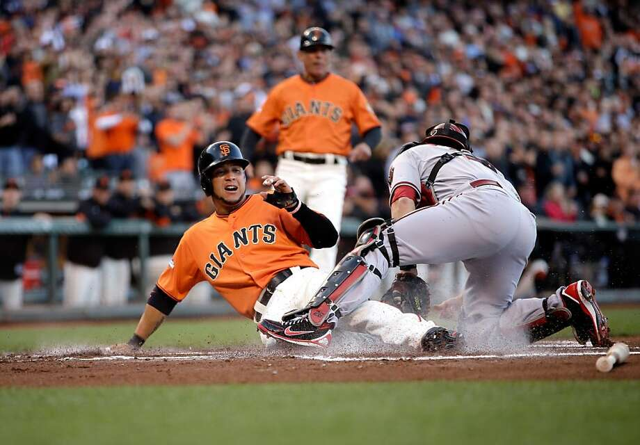 Gregor Blanco slides home safely on Buster Posey's double as Arizona catcher Miguel Montero can't handle the throw. Photo: Ezra Shaw, Getty Images