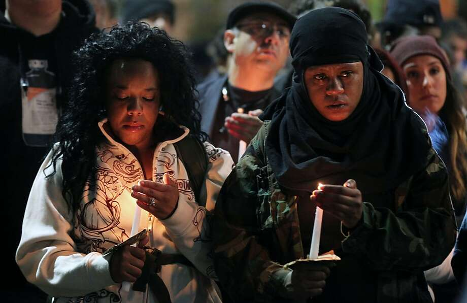 Two women hold candles at a candlelight ceremony to honor Trayvon Martin at the Fruitvale BART station. Several hundred people protested the verdict in the George Zimmerman trial, chanting slogans while walking from Frank Ogawa Plaza to the Fruitvale BART station in Oakland on Friday July 19, 2013. Photo: Lance Iversen, The Chronicle