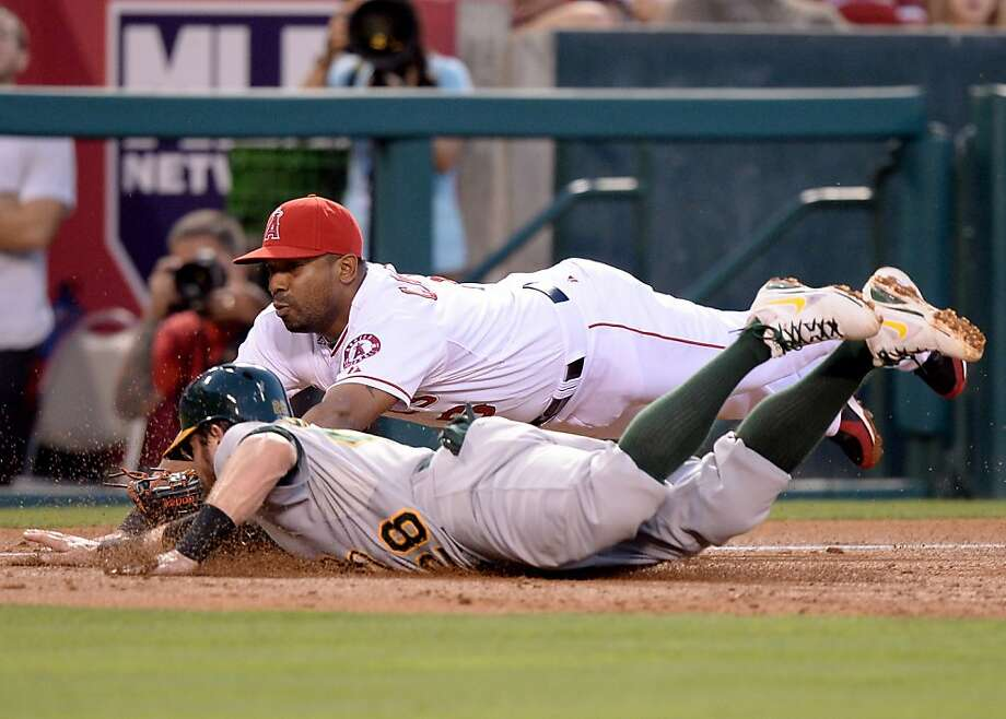 ANAHEIM, CA - JULY 19:  Alberto Callaspo #6 of the Los Angeles Angels dives to tag out Eric Sogard #28 of the Oakland Athletics at third base to end the third inning at Angel Stadium of Anaheim on July 19, 2013 in Anaheim, California.  (Photo by Harry How/Getty Images) Photo: Harry How, Getty Images