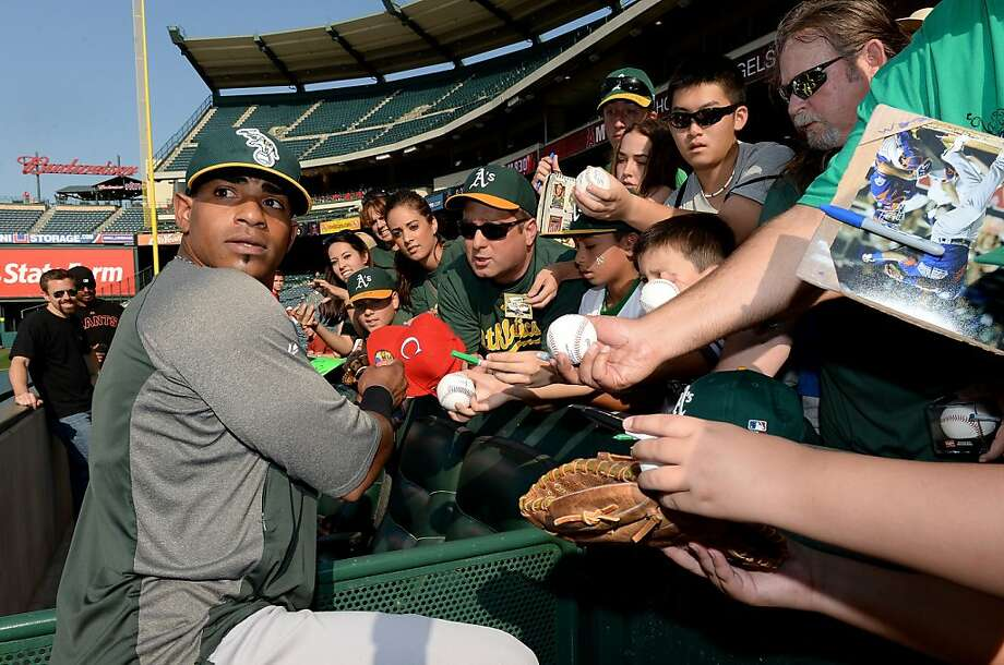 ANAHEIM, CA - JULY 19:  Yoenis Cespedes #52 of the Oakland Athletics looks back to the field as he signs autographs for fans prior to the game against the Los Angeles Angels at Angel Stadium of Anaheim on July 19, 2013 in Anaheim, California.  (Photo by Harry How/Getty Images) Photo: Harry How, Getty Images