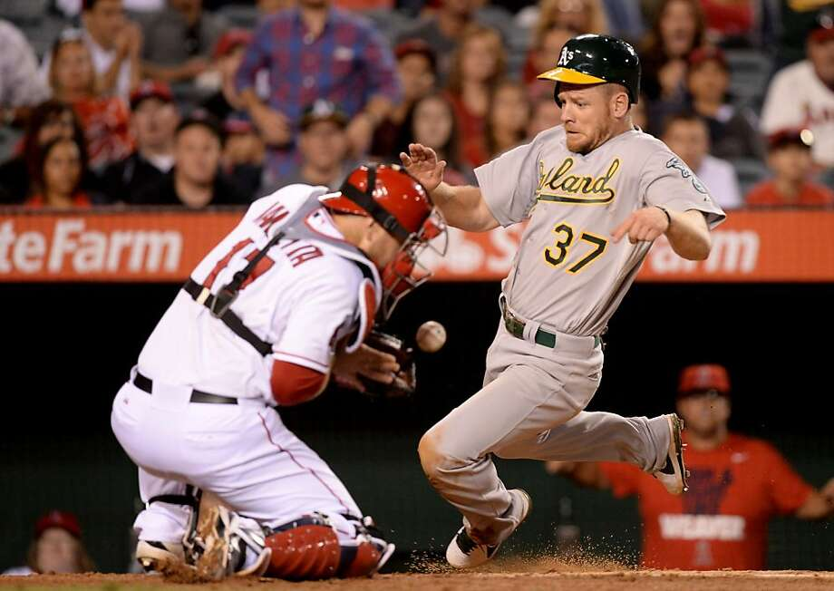 ANAHEIM, CA - JULY 19:  Brandon Moss #37 of the Oakland Athletics scores a run in front of Chris Iannetta #17 of the Los Angeles Angels to trail 4-1 during the ninth inning at Angel Stadium of Anaheim on July 19, 2013 in Anaheim, California.  (Photo by Harry How/Getty Images) Photo: Harry How, Getty Images