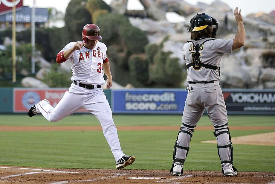 Los Angeles Angels' J.B. Shuck, left, scores on a double hit by Josh Hamilton as Oakland Athletics catcher John Jaso waits for the throw during the first inning of a baseball game on Friday, July 19, 2013, in Anaheim, Calif. (AP Photo/Jae C. Hong) Photo: Jae C. Hong, Associated Press