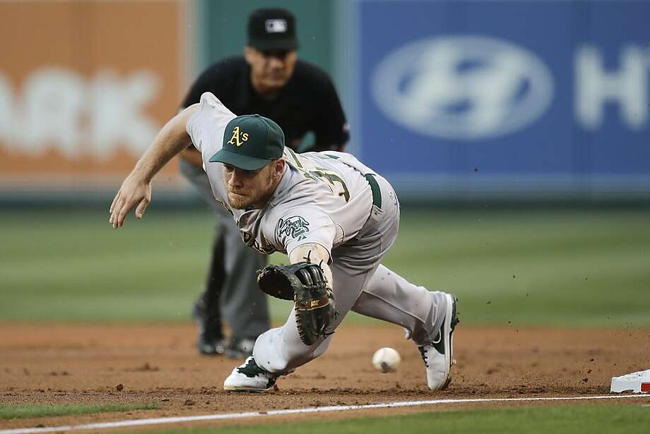 Oakland Athletics first baseman Brandon Moss misses a throw during the first inning of a baseball game against the Los Angeles Angels on Friday, July 19, 2013, in Anaheim, Calif. (AP Photo/Jae C. Hong) Photo: Jae C. Hong, Associated Press