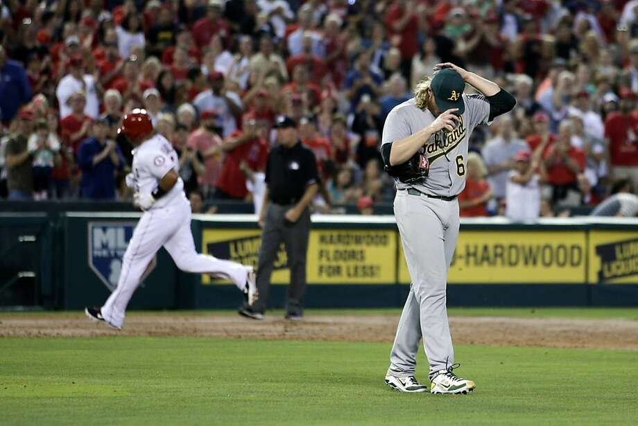 Oakland Athletics starting pitcher A.J. Griffin, right, adjusts his hat as Los Angeles Angels' Albert Pujols, background left, rounds the bases after hitting a home run during the third inning of a baseball game on Friday, July 19, 2013, in Anaheim, Calif. (AP Photo/Jae C. Hong) Photo: Jae C. Hong, Associated Press