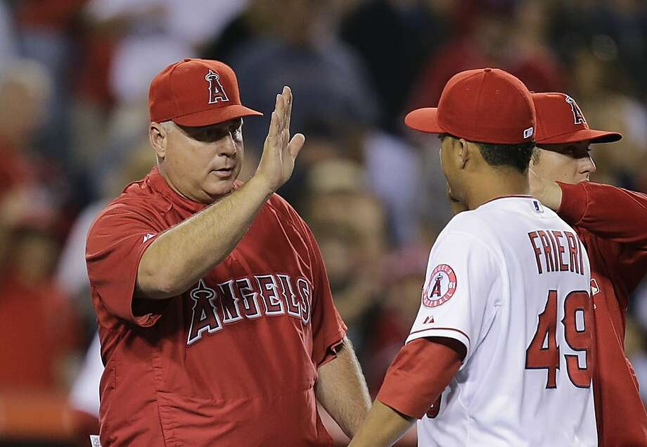 Los Angeles Angels manager Mike Scioscia, left, high-fives relief pitcher Ernesto Frieri as they celebrate the team's 4-1 win against the Oakland Athletics after a baseball game on Friday, July 19, 2013, in Anaheim, Calif. (AP Photo/Jae C. Hong) Photo: Jae C. Hong, Associated Press