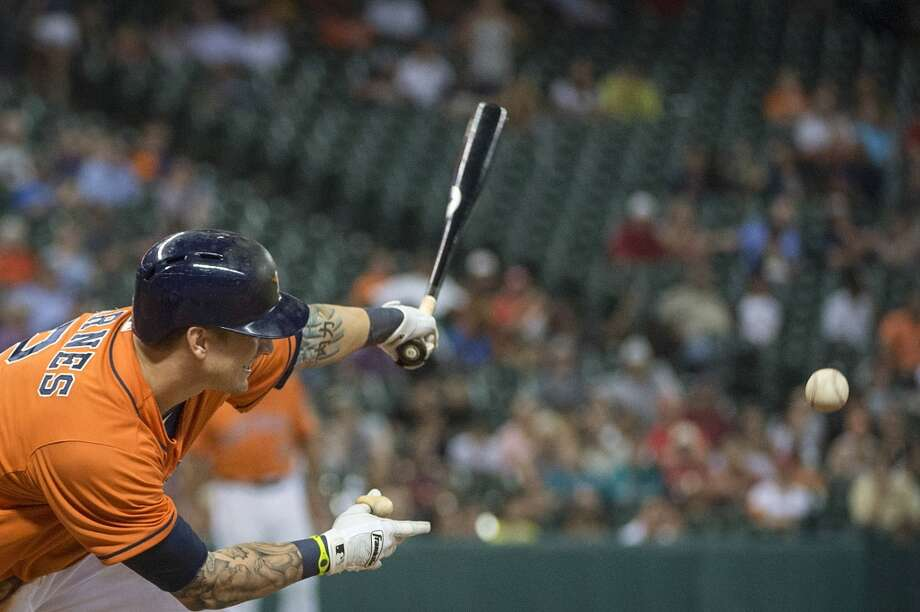 Astros center fielder Brandon Barnes hits an infield single during the ninth inning.