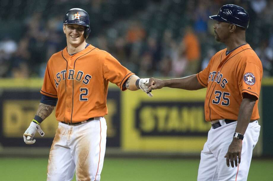 Astros center fielder Brandon Barnes gets a hand from first base coach Dave Clark after hitting an infield single during the ninth inning.