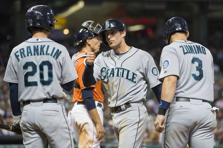 Mariners shortstop Brad Miller celebrates with second baseman Nick Franklin and catcher Mike Zunino after hitting a home run.