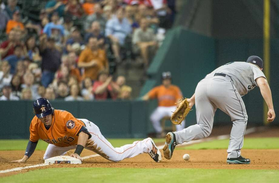 Astros shortstop Jake Elmore is safe at third as the ball gets away from Mariners third baseman Kyle Seager.