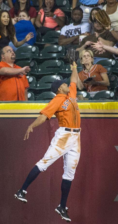 Astros right fielder Justin Maxwell can't make the play as a home run by Mariners shortstop Brad Miller heads into the stands.