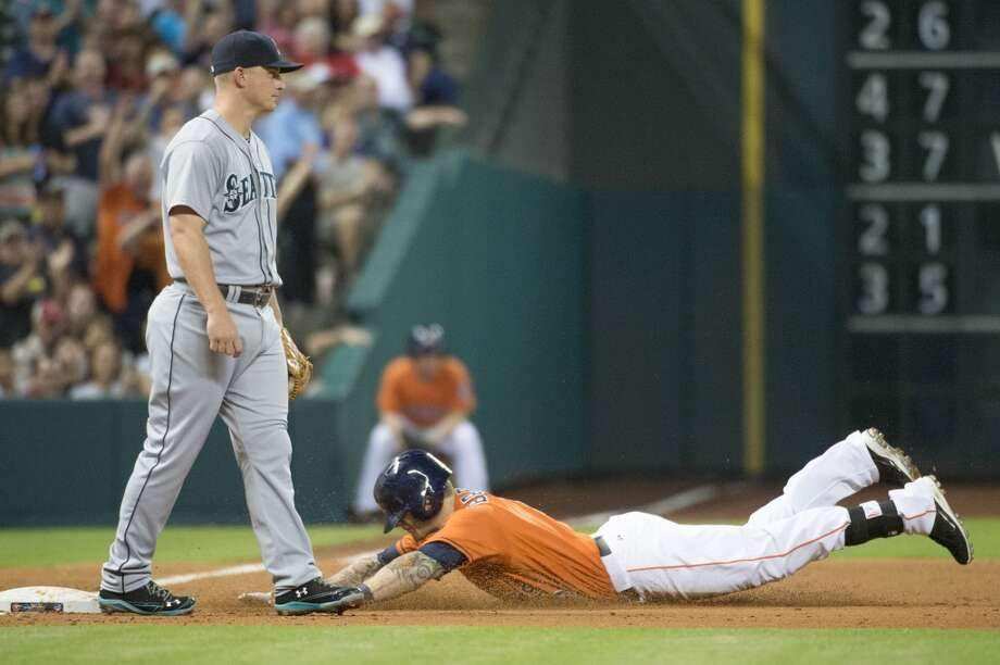 Astros center fielder Brandon Barnes slides into third base with a triple in the fourth inning.