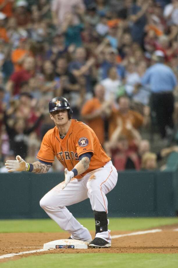 Astros center fielder Brandon Barnes celebrates after sliding into third base with a triple in the fourth inning.